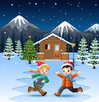 Joyeux enfants jouant devant la maison enneigée au jour de noël
