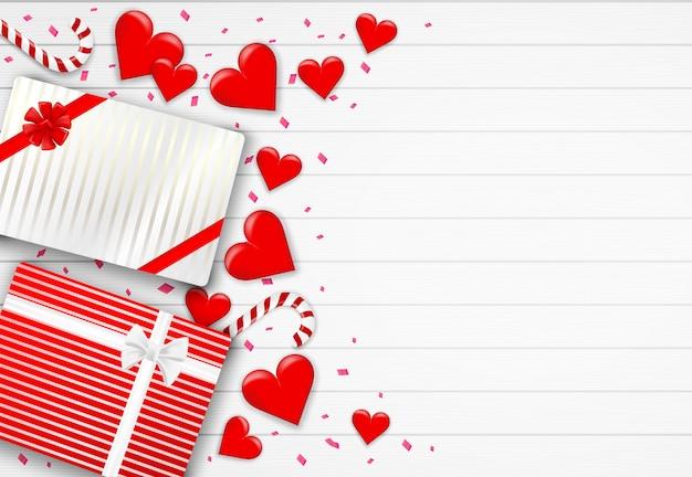 Joyeux fond de saint valentin. avec coeur, boîte-cadeau et confettis de feuille rose sur fond de bois blanc. .