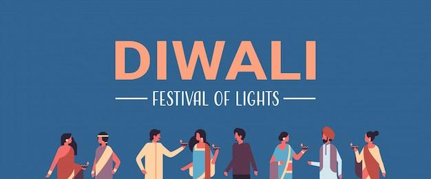 Joyeux groupe d'indiens diwali portant des vêtements traditionnels nationaux tenant une bannière de lampe à huile