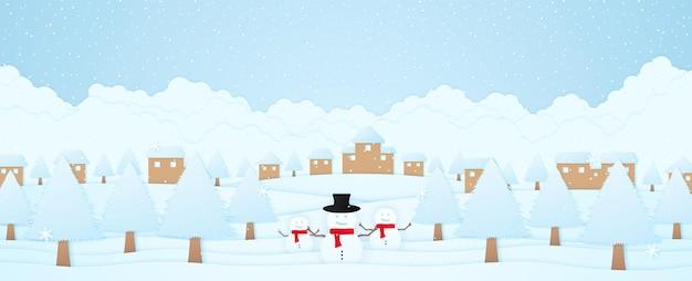 Joyeux noël bonhomme de neige et arbres de bienvenue sur la neige paysage d'hiver village sur la colline et chute de neige