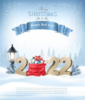 Joyeux noël et bonne année 2022. numéros 3d dorés avec un sac rouge plein de cadeaux sur fond de paysage d'hiver. vecteur
