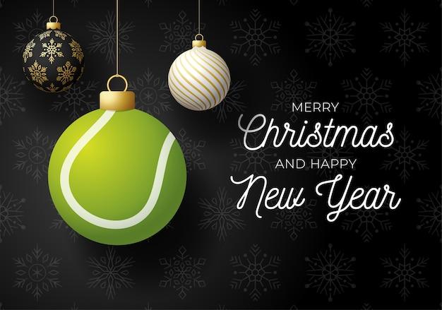Joyeux noël et bonne année carte postale de sports de luxe. balle de tennis comme boule de noël sur fond noir.