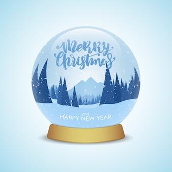 Joyeux noël et bonne année snow globe avec paysage de montagnes d'hiver isolé sur fond bleu clair