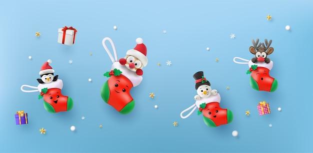 Joyeux noël et bonne et bonne année. père noël, bonhomme de neige, renne et pingouin dans la chaussette rouge