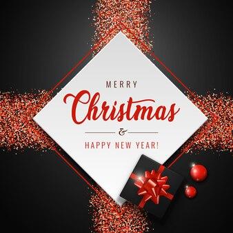 Joyeux noël carte avec carré blanc, boules rouges, cadeau réaliste et paillettes scintille sur fond sombre.