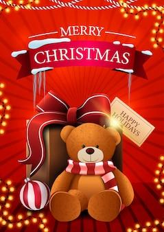 Joyeux noël, carte postale verticale rouge avec guirlande et cadeau avec ours en peluche