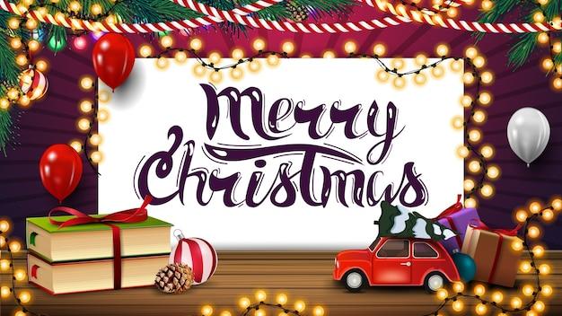Joyeux noël, carte postale de voeux avec feuille de papier, guirlandes, ballons, livres et voiture vintage rouge transportant l'arbre de noël