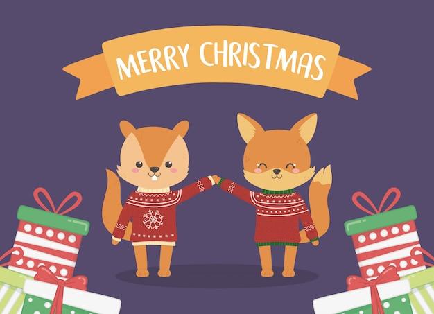 Joyeux noël célébration écureuil et renard avec pulls rouges et pile de cadeaux
