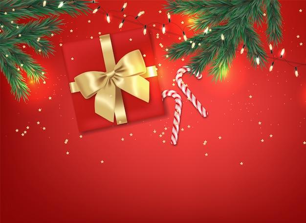 Joyeux noël, éléments de design décoratif, hiver, fond de célébration, lumières réalistes, bonbons de noël, cadeau rouge avec des branches d'arc et de sapin