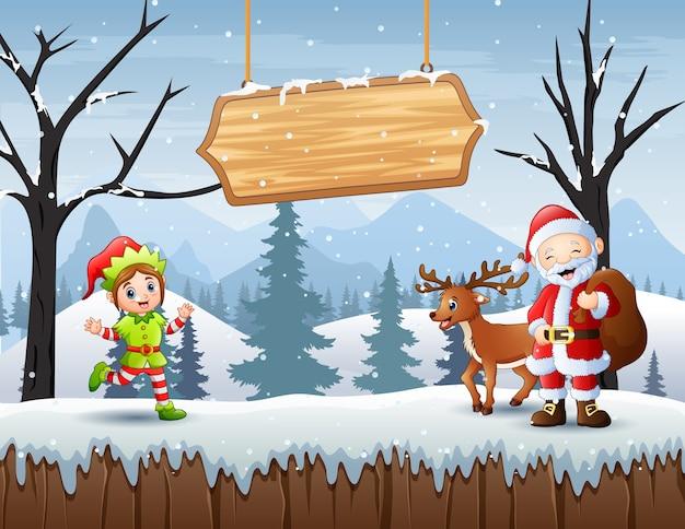 Joyeux noël avec le père noël et l'elfe dans le paysage d'hiver