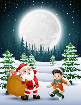 Joyeux noël avec le père noël tenant des sacs de cadeau et un petit garçon en hiver