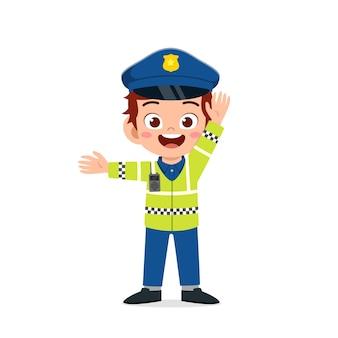 Joyeux petit garçon mignon portant un uniforme de police et gérant le trafic