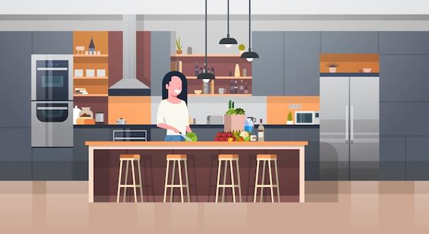 Kithcen moderne intérieur et jeune femme cuisine salade