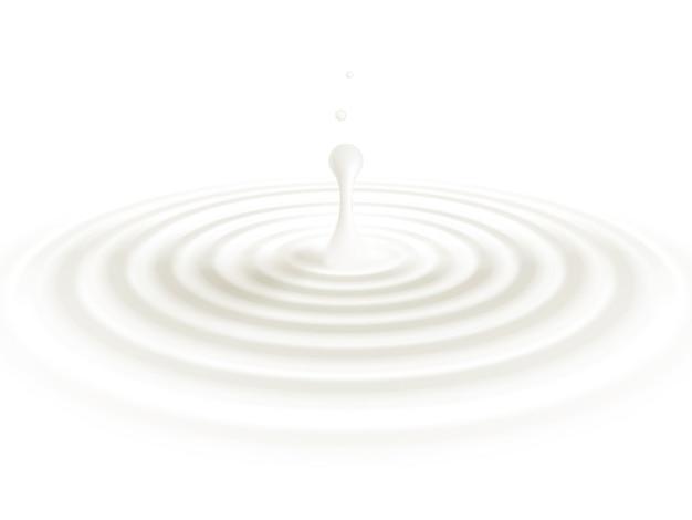Lait ou crème liquide beige goutte sur fond blanc.