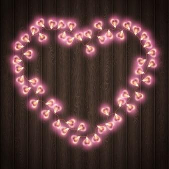 Lampe en forme de coeur pour la décoration sur fond de bois.
