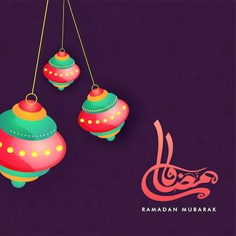 Lanternes colorées suspendues et texte calligraphique arabe ramadan moubarak sur fond violet.
