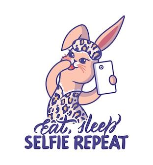 Lapin de dessin animé en imprimé léopard et citation de lettrage mangez le sommeil répétez selfie