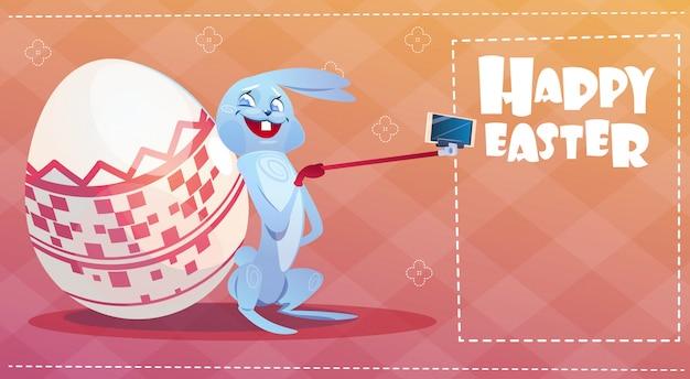 Lapin prenant des oeufs décorés de carte de voeux de photo de lapin de vacances de pâques de selfie