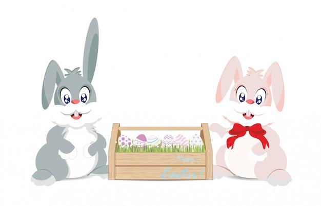 Lapins de pâques et oeufs de pâques dans une boîte en bois pour la décoration
