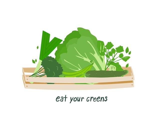 Légumes dans une boîte en bois et mots écologiques eat your greens