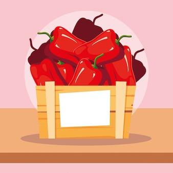 Légumes frais au paprika rouge dans une caisse en bois