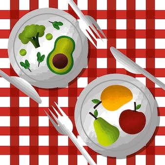 Légumes et fruits sur les plats fourchette couteau sur la nappe
