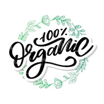 Lettrage de brosse organique. mot dessiné à la main organique avec des feuilles vertes.