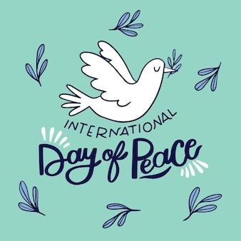 Lettrage de jour de paix et oiseau dessiné