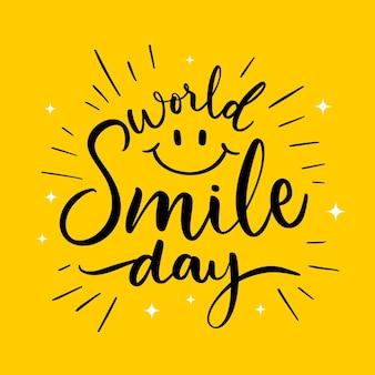 Lettrage de la journée mondiale du sourire avec un visage heureux