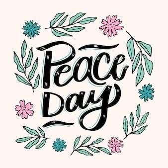 Lettrage de la journée de la paix avec des feuilles et des fleurs illustrées