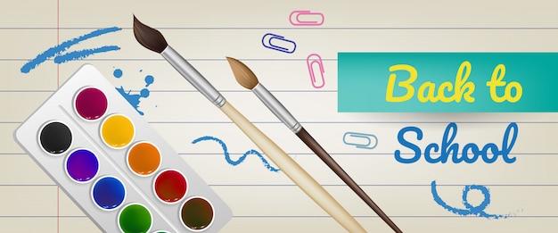 Lettrage de rentrée scolaire sur du papier ligné avec des peintures et des pinceaux