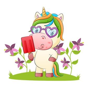 La licorne mignonne tient une délicieuse crème glacée avec l'illustration aux couleurs vives