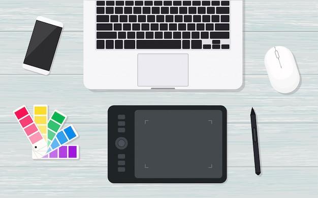 Lieu de travail de concepteur vue de dessus avec tablette graphique. mise à plat sur fond de bois