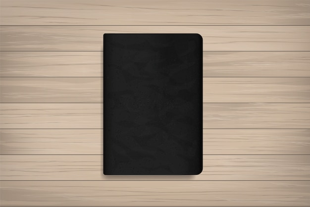 Livre avec couverture noire sur bois.