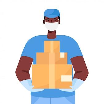 Un livreur dans un masque médical de protection et des gants tient une boîte en carton dans ses mains.