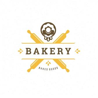 Logo de boulangerie avec des rouleaux à pâtisserie et des silhouettes de beignets