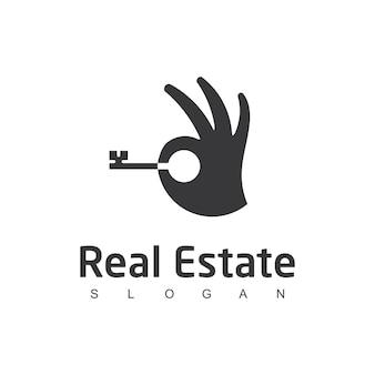 Logo de l'immobilier avec la main et le symbole de la clé