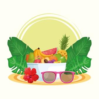 Lunettes de soleil avec un bol de fruits et de feuilles tropicales