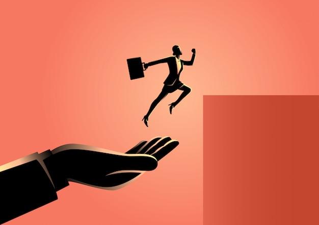 Main aidant une femme d'affaires à sauter plus haut