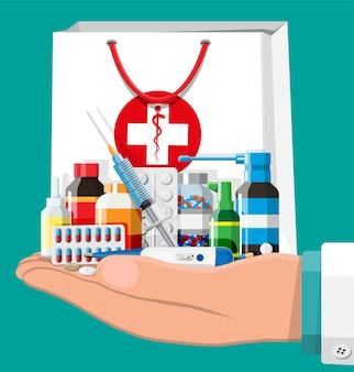 Main avec collection de médicaments dans un sac