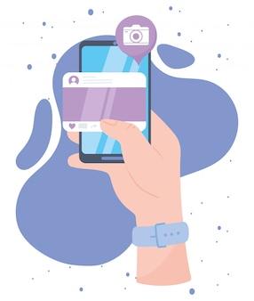 Main avec la communication et les technologies de réseau social de l'application de la caméra du site web du smartphone