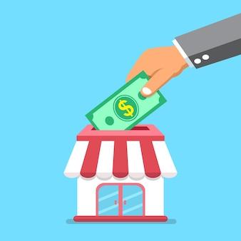 Main de concept d'entreprise mettre de l'argent dans le magasin