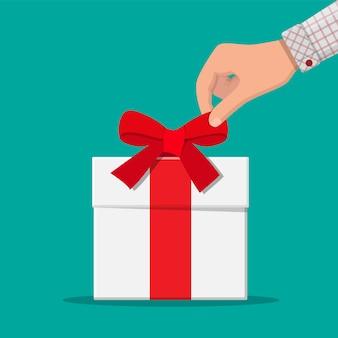 La main délie le noeud de ruban sur une boîte cadeau blanche.