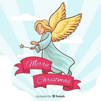 Main dessinée ange de noël avec des ailes