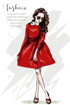 Main dessinée belle femme en robe rouge.