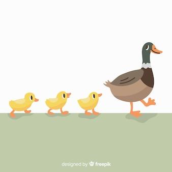 Main dessinée canard mère et canetons sur l'herbe