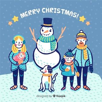 Main dessinée famille avec bonhomme de neige fond de noël