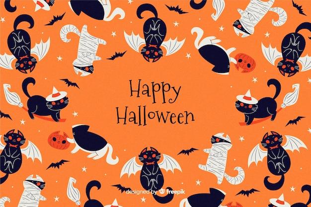 Main dessinée fond d'halloween avec des chats noirs