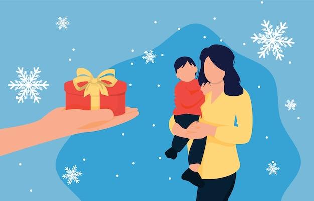 Main donnant un cadeau à la mère avec l'enfant. joyeux noël, surprise en famille.