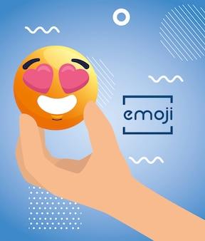 Main avec emoji charmant, visage jaune avec coeurs dans les yeux,
